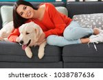 Stock photo young woman with dog indoors friendship between pet and owner 1038787636