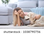 Stock photo portrait of happy woman with her dog at home 1038790756