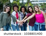 Small photo of 5 latin and caucasian and african american women keep together outdoors in the summer in the city
