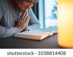 a senior woman praying at home. | Shutterstock . vector #1038814408