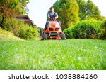 gardener driving a riding lawn... | Shutterstock . vector #1038884260