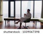 man in bathrobe drinks coffee... | Shutterstock . vector #1039067398