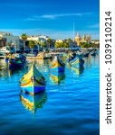Small photo of MARSAXLOKK, MALTA - NOVEMBER 11, 2015: Colorful painted wood boats with the typical protective eyes on a sunny day in Marsaxlokk, Malta.