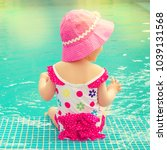 baby sitting near swimming pool. | Shutterstock . vector #1039131568