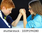Small photo of Young Boy And Girl Having An Arm Wrestle. Brother And Sister In A Rival Battle Of Strength