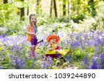 kids with bluebell flowers ... | Shutterstock . vector #1039244890