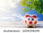 pink piggy bank lay on a wooden ... | Shutterstock . vector #1039298290
