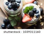 yogurt and granola with berries ... | Shutterstock . vector #1039311160