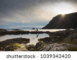 Silhouette of a person running across rocks by the water. Photography taken in Bremanger, Norway during sunset.