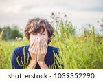 young man sneezes because of an ... | Shutterstock . vector #1039352290