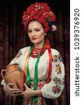 Small photo of Portrait of attractive woman standing in traditional Slavic costume, wearing embroidered blouse, flower crown with ribbons, red necklace, carrying clay jug, looking aside over dark brown background