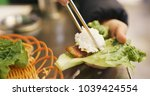 woman wrapping grilled korean...   Shutterstock . vector #1039424554
