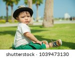 the thai kid sits on the grass... | Shutterstock . vector #1039473130