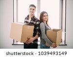 couple with boxes moving into... | Shutterstock . vector #1039493149