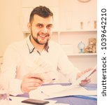 Small photo of Manager is signing agreement papers of financial nature at home.