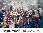 Small photo of Fun in motion. Group of beautiful young people throwing colorful confetti while dancing and looking happy