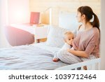 one year old baby eating mother'... | Shutterstock . vector #1039712464
