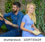 Small photo of Romantic date and love concept. Couple in love sits outdoor, nature background, defocused. Girl with happy face listen bearded man reading poems. Romantic couple holds old books with poems about love.
