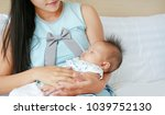 close up mother carry sleeping... | Shutterstock . vector #1039752130