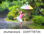 kid playing out in the rain.... | Shutterstock . vector #1039778734