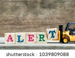 Small photo of Yellow toy forklift holds letter block T to complete word alert on wood background