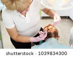 Small photo of Dentist woman makes anesthetizing injection within a patient's mouth. Injection techniques to anesthetize the tooth in the modern dental clinic