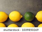 one lime among lemons on gray... | Shutterstock . vector #1039850269