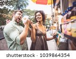 couple buying a hot dog in a... | Shutterstock . vector #1039864354
