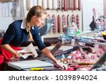 sales woman in butcher shop... | Shutterstock . vector #1039894024