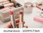 a person holds two lipsticks....   Shutterstock . vector #1039917364