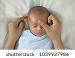 mother hand massaging baby face ...   Shutterstock . vector #1039937986