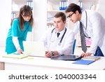 three doctors discussing scan... | Shutterstock . vector #1040003344