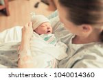 mother in hospital holding her... | Shutterstock . vector #1040014360