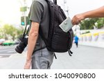 Small photo of closeup pickpocket's hand stealing purse from backpacker