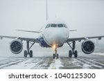 airliner on runway in blizzard. ... | Shutterstock . vector #1040125300