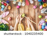 mother and child painting eggs. ... | Shutterstock . vector #1040235400