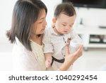 mother holding milk bottle with ... | Shutterstock . vector #1040292454