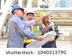 Small photo of The male engineer is checking the blueprint and instructs the project leader to accomplish the goal