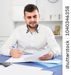 Small photo of Businessman is signing agreement papers of financial nature at home.