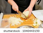 woman chopping cabbage on the... | Shutterstock . vector #1040443150