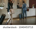 Stock photo woman carrying suitcase and talking on mobile phone in a hotel lobby traveler female walking with 1040453713