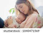 young mother  holding tenderly... | Shutterstock . vector #1040471569