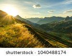 Stock photo beautiful sunrise and layered mountain silhouettes in early morning lechtal and allgau alps 1040488174