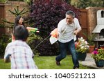 family are having a water fight ...   Shutterstock . vector #1040521213