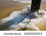 chains on the column frozen in... | Shutterstock . vector #1040534923