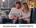 a couple looks at the tablet... | Shutterstock . vector #1040578870