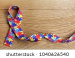 Small photo of World Autism awareness and pride day or month with Puzzle pattern ribbon on wooden background.