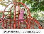 adorable little girl climbing... | Shutterstock . vector #1040668120