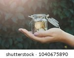hand holding glass jar with... | Shutterstock . vector #1040675890