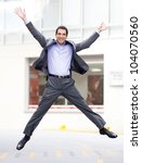 Excited business man jumping and looking very happy - stock photo